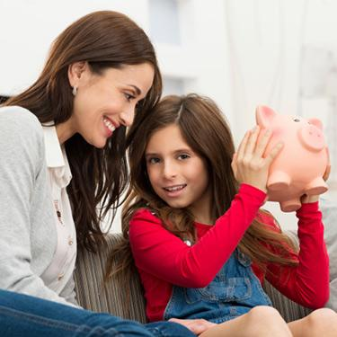 Mother-looking-at-daughter-holding-piggybank_web