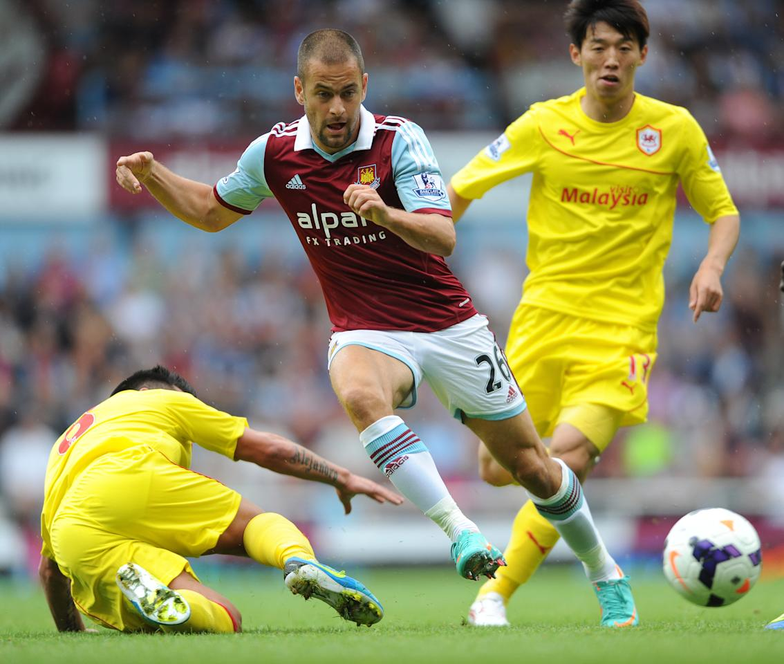 West Ham United's Joe Cole gets between two Cardiff City defenders during the Barclays Premier League match at Upton Park, London.
