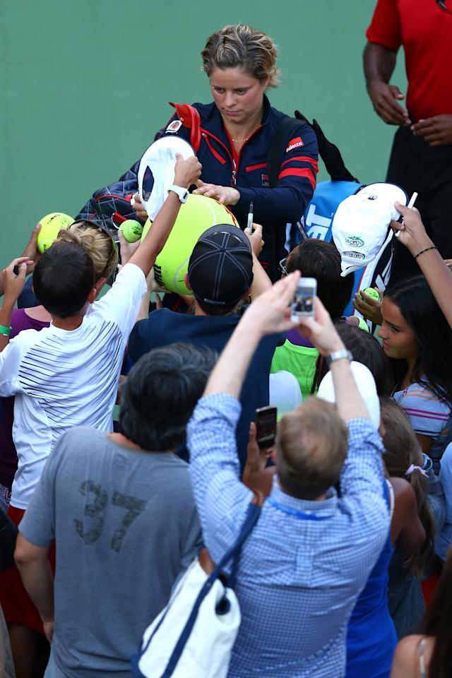 NEW YORK, NY - AUGUST 29:  Kim Clijsters of Belgium signs autographs for fans as she leaves the court following her defeat to Laura Robson of Great Britain after their women's singles second round match on Day Three of the 2012 US Open at USTA Billie Jean King National Tennis Center on August 29, 2012 in the Flushing neigborhood of the Queens borough of New York City.  (Photo by Al Bello/Getty Images)