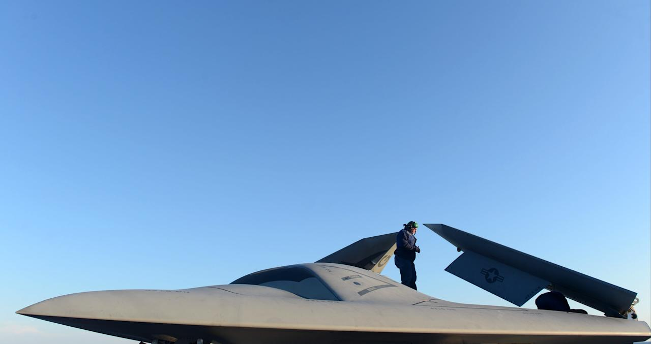 ATLANTIC OCEAN - MAY 14:  In this handout released by the U.S. Navy, Northrop Grumman personnel conduct pre-operational tests on an X-47B Unmanned Combat Air System (UCAS) demonstrator on the flight deck of the aircraft carrier USS George H.W. Bush (CVN 77) May 14, 2013 in the Atlantic Ocean. George H.W. Bush is scheduled to be the first aircraft carrier to catapult-launch an unmanned aircraft from its flight deck. The Navy plans to have unmanned aircraft on each of its carriers to be used for surveillance and be armed and used in combat roles.  (Photo by Mass Communication Specialist 2nd Class Timothy Walter/U.S. Navy via Getty Images)