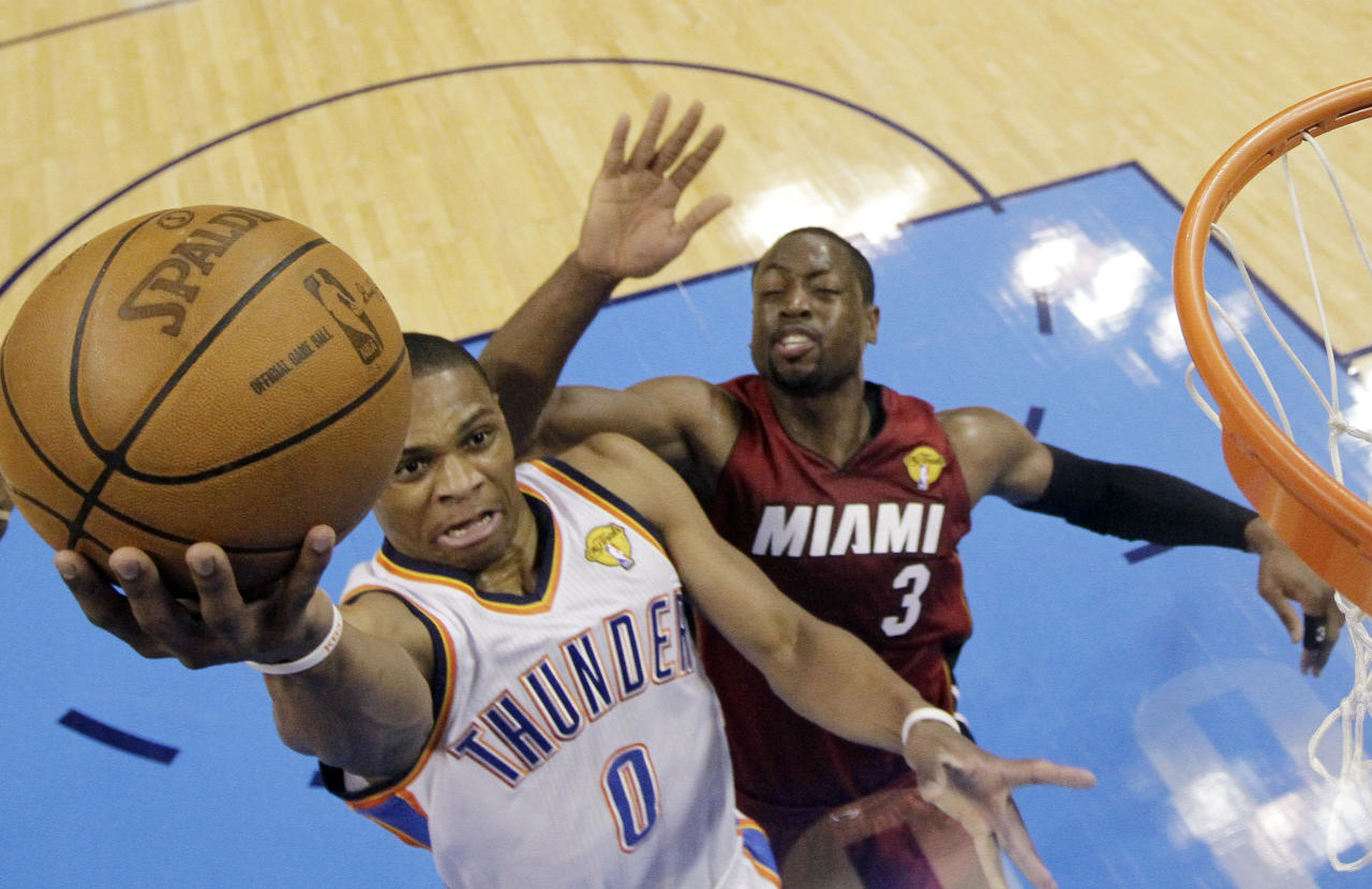 Oklahoma City Thunder point guard Russell Westbrook (0) shoots as Miami Heat shooting guard Dwyane Wade defends during the first half at Game 1 of the NBA finals basketball series, Tuesday, June 12, 2012, in Oklahoma City. (AP Photo/Jeff Roberson, Pool)