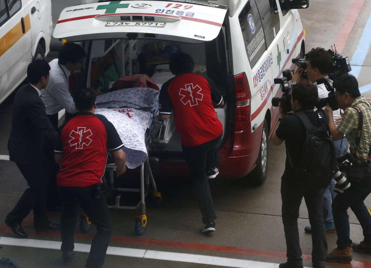 A passenger of Asiana flight 214 is wheeled into an ambulance on a stretcher upon her arrival at the Incheon Airport in Incheon, west of Seoul Monday, July 8, 2013. The Asiana flight crashed upon landing Saturday, July 6, at San Francisco International Airport, and two of the 307 passengers aboard were killed. (AP Photo/Kim Hong-Ji, Pool)