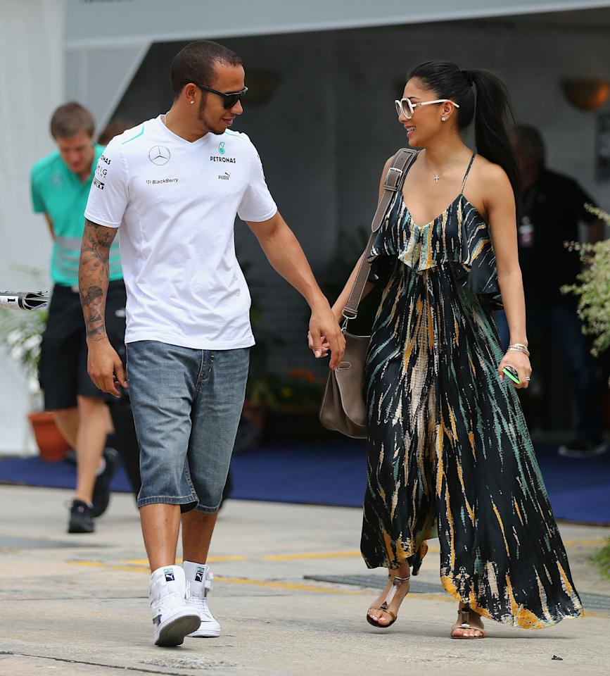 KUALA LUMPUR, MALAYSIA - MARCH 24:  Lewis Hamilton of Great Britain and Mercedes GP and his girlfriend Nicole Scherzinger of the Pussycat Dolls arrive in the paddock before the Malaysian Formula One Grand Prix at the Sepang Circuit on March 24, 2013 in Kuala Lumpur, Malaysia.  (Photo by Clive Mason/Getty Images)
