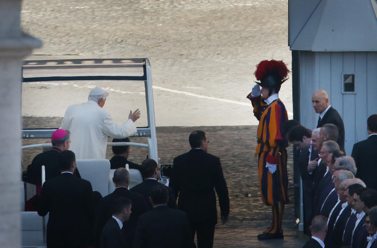 VATICAN CITY, VATICAN - FEBRUARY 27:  Pope Benedict XVI waves to a Swiss Guard as he leaves St Peter's Square on February 27, 2013 in Vatican City, Vatican.  The Pontiff has attended his last weekly public audience before stepping down tomorrow. Pope Benedict XVI has been the leader of the Catholic Church for eight years and is the first Pope to retire since 1415. He cites ailing health as his reason for retirement and will spend the rest of his life in solitude away from public engagements.  (Photo by Peter Macdiarmid/Getty Images)