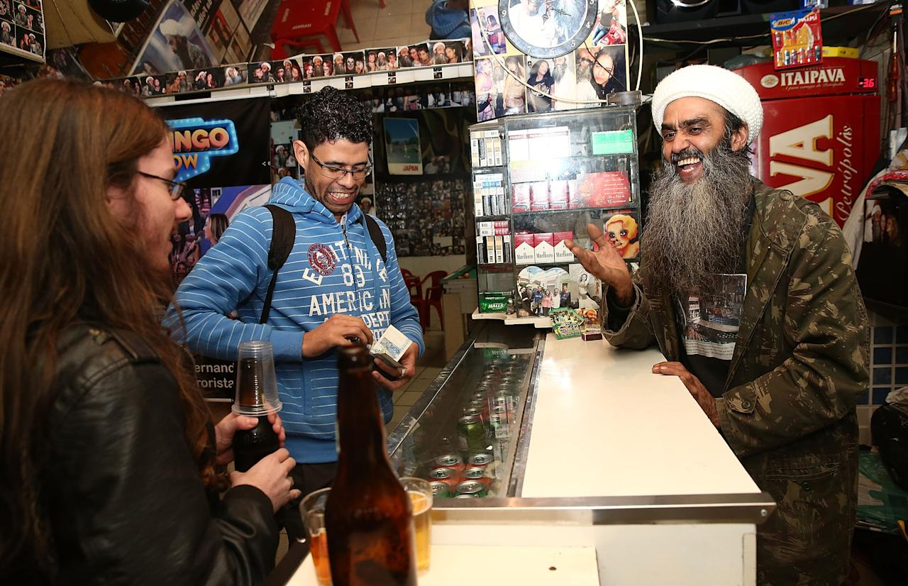 SAO PAULO, BRAZIL - APRIL 29: Osama bin Laden lookalike Ceara Francisco Helder Braga Fernandes (R) serves customers in his 'Bar do Bin Laden' on April 29, 2014 in Sao Paulo, Brazil. Braga says he was known as the 'Beard Man' before 9/11 but became known as a Bin Laden lookalike following the 9/11 attacks. He says he is Christian and continues to play the role to support his business. (Photo by Mario Tama/Getty Images)