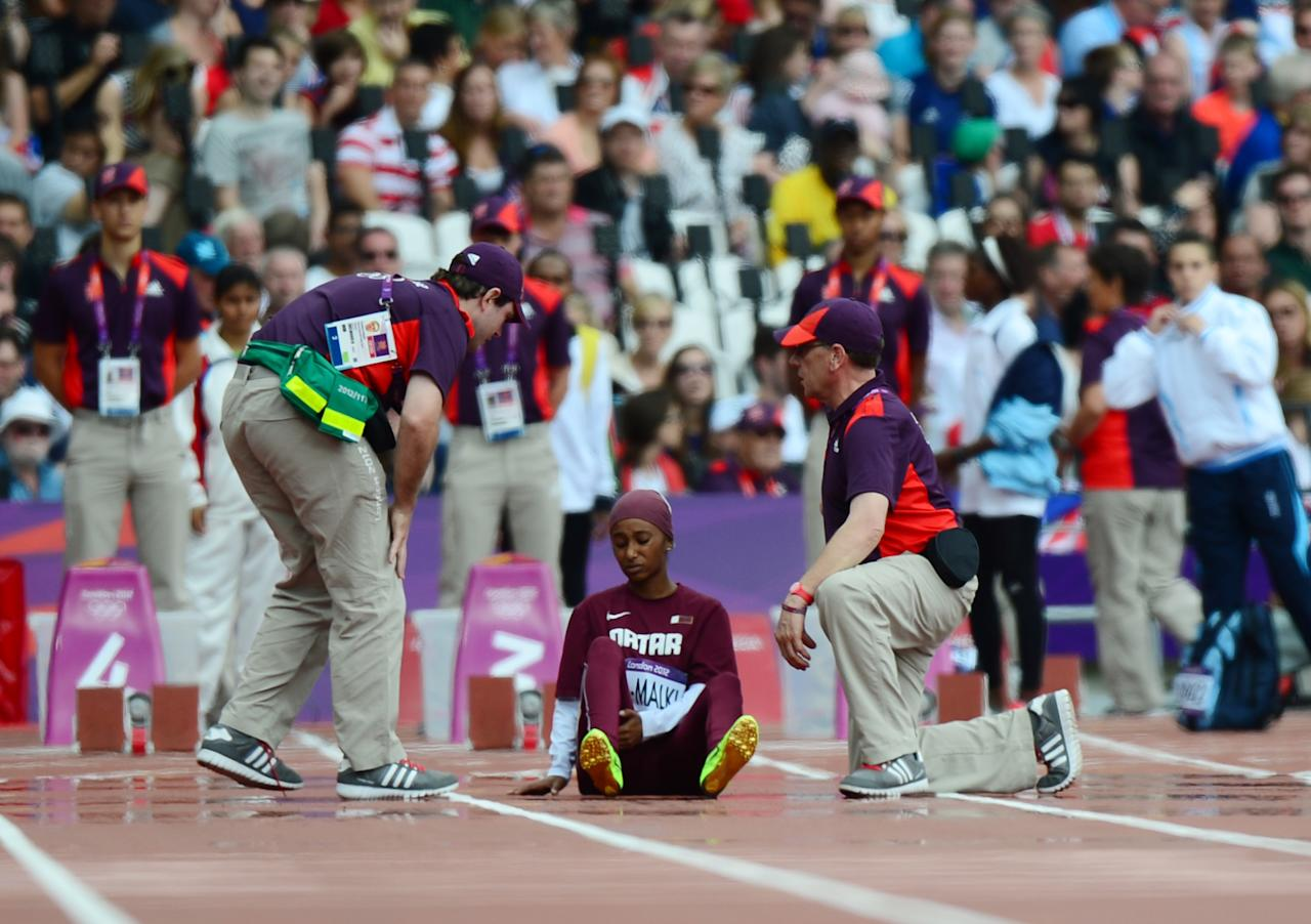 Qatar's Noor Hussain Al-Malki gets medical assistance after suffering an injury during the women's 100m heats at the athletics event during the London 2012 Olympic Games on August 3, 2012 in London.  AFP PHOTO / OLIVIER MORINOLIVIER MORIN/AFP/GettyImages