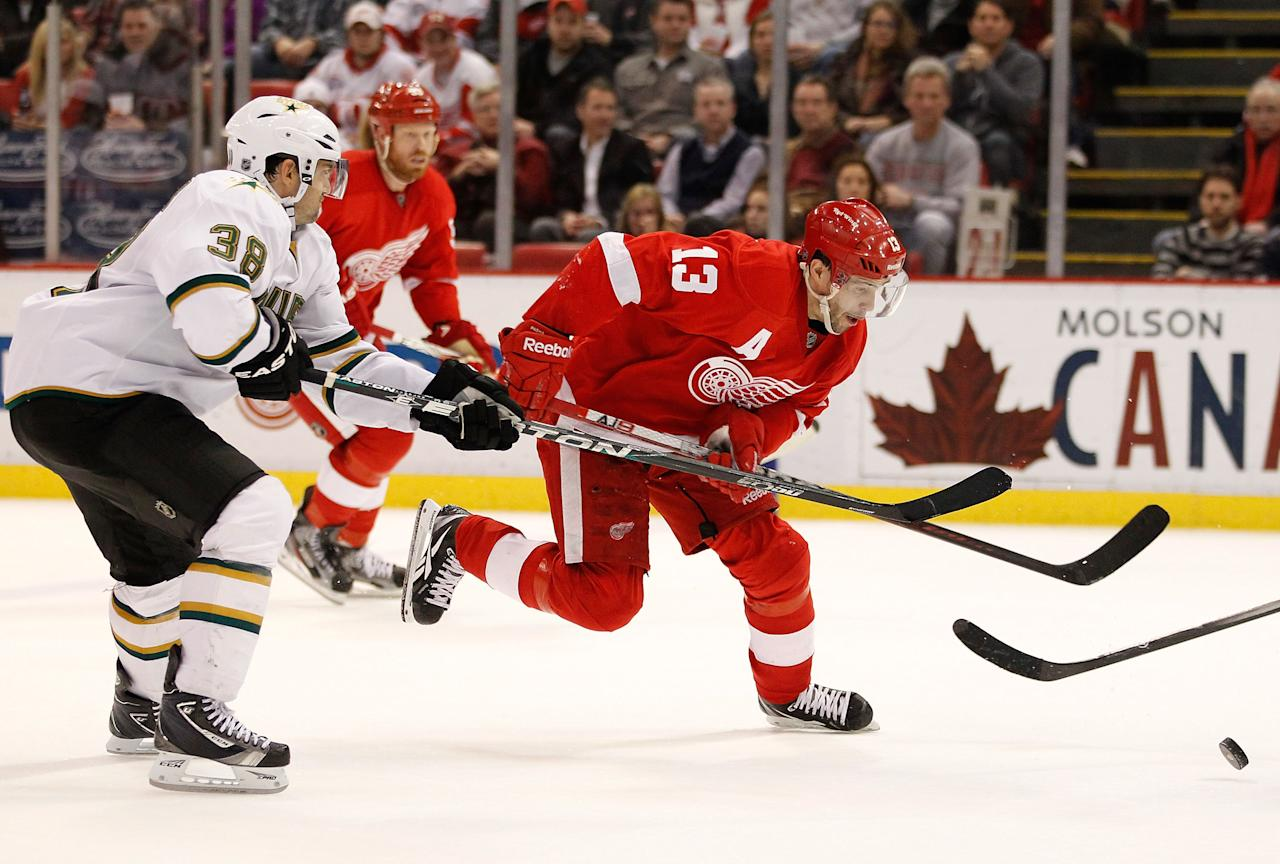 DETROIT, MI - FEBRUARY 14: Pavel Datsyuk #13 of the Detroit Red Wings tries to control the puck in front of Vernon Fiddler #38 of the Dallas Stars at Joe Louis Arena on February 14, 2012 in Detroit, Michigan. Detroit defeated Dallas 3-1. The win set a NHL record for the most consecutive home victories with 21. (Photo by Gregory Shamus/Getty Images)