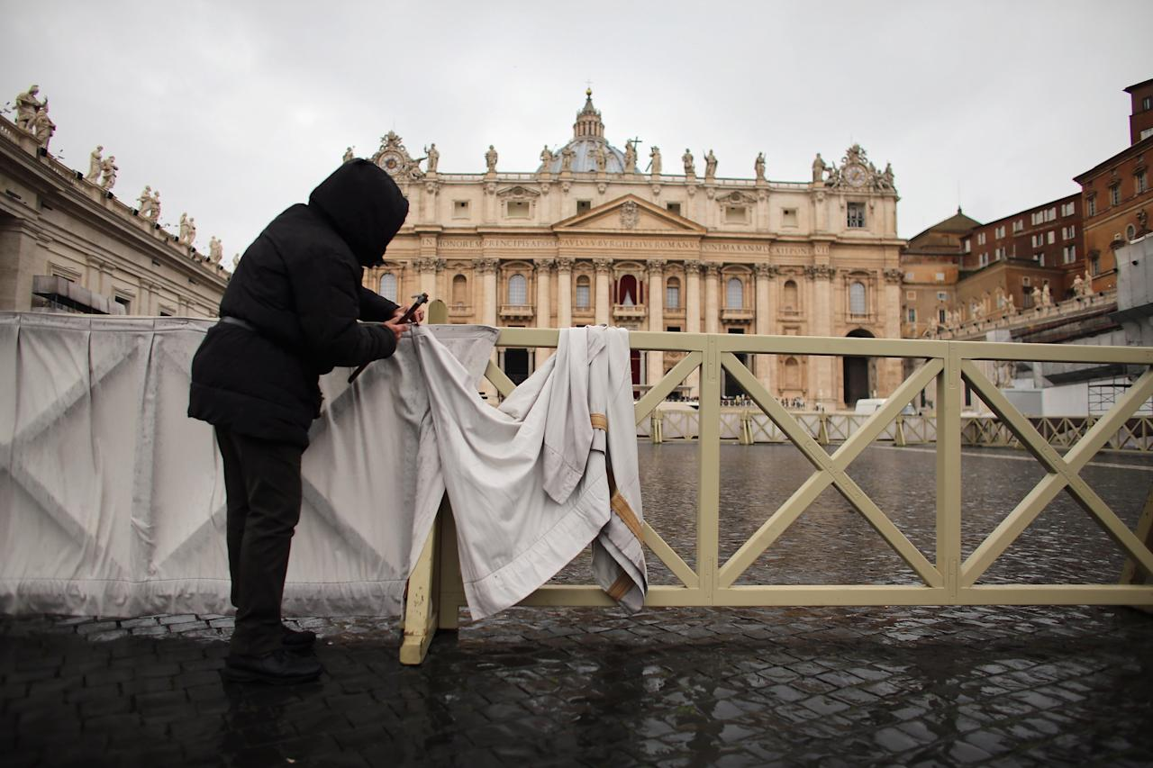 VATICAN CITY, VATICAN - MARCH 18:  A worker hangs bunting on a crowd control fence as he helps prepare Saint Peter Square for the inauguration mass on March 18, 2013 in Vatican City, Vatican. The Inauguration Mass for Pope Francis will take place on March 19, the feast day for St. Joseph. (Photo by Joe Raedle/Getty Images)