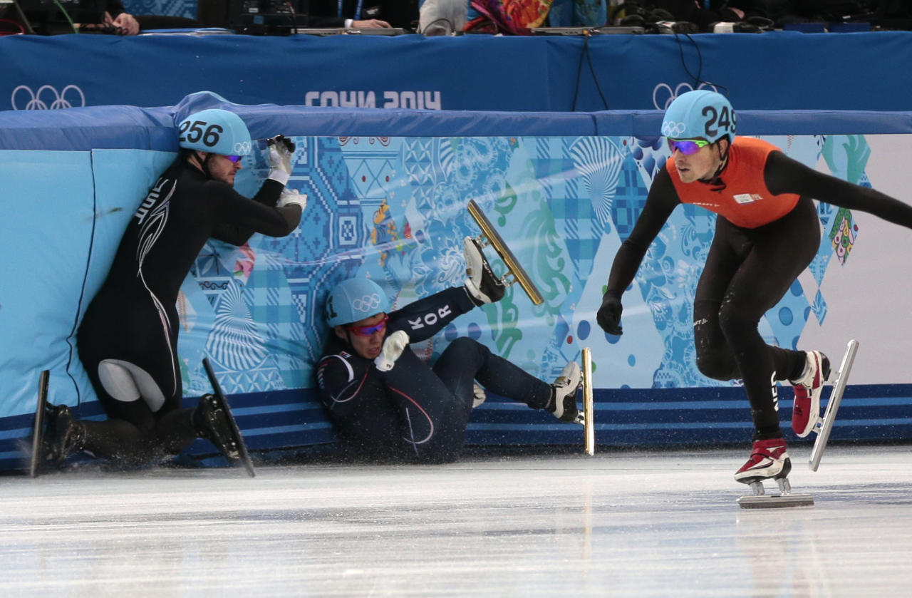 Lee Ho-suk of South Korea, left, and Eduardo Alvarez of the United States, centre, crash out alongside Freek Van Der Wart of the Netherlands as they compete in a men's 5000m short track speedskating relay semifinal at the Iceberg Skating Palace during the 2014 Winter Olympics, Thursday, Feb. 13, 2014, in Sochi, Russia. (AP Photo/Ivan Sekretarev)