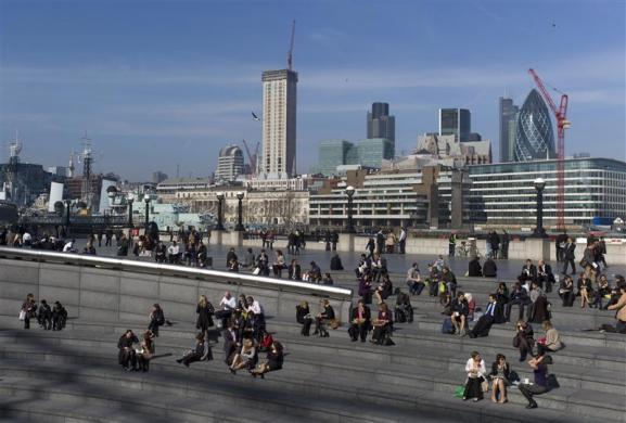 People eat their lunch along the south bank in London March 12, 2012.