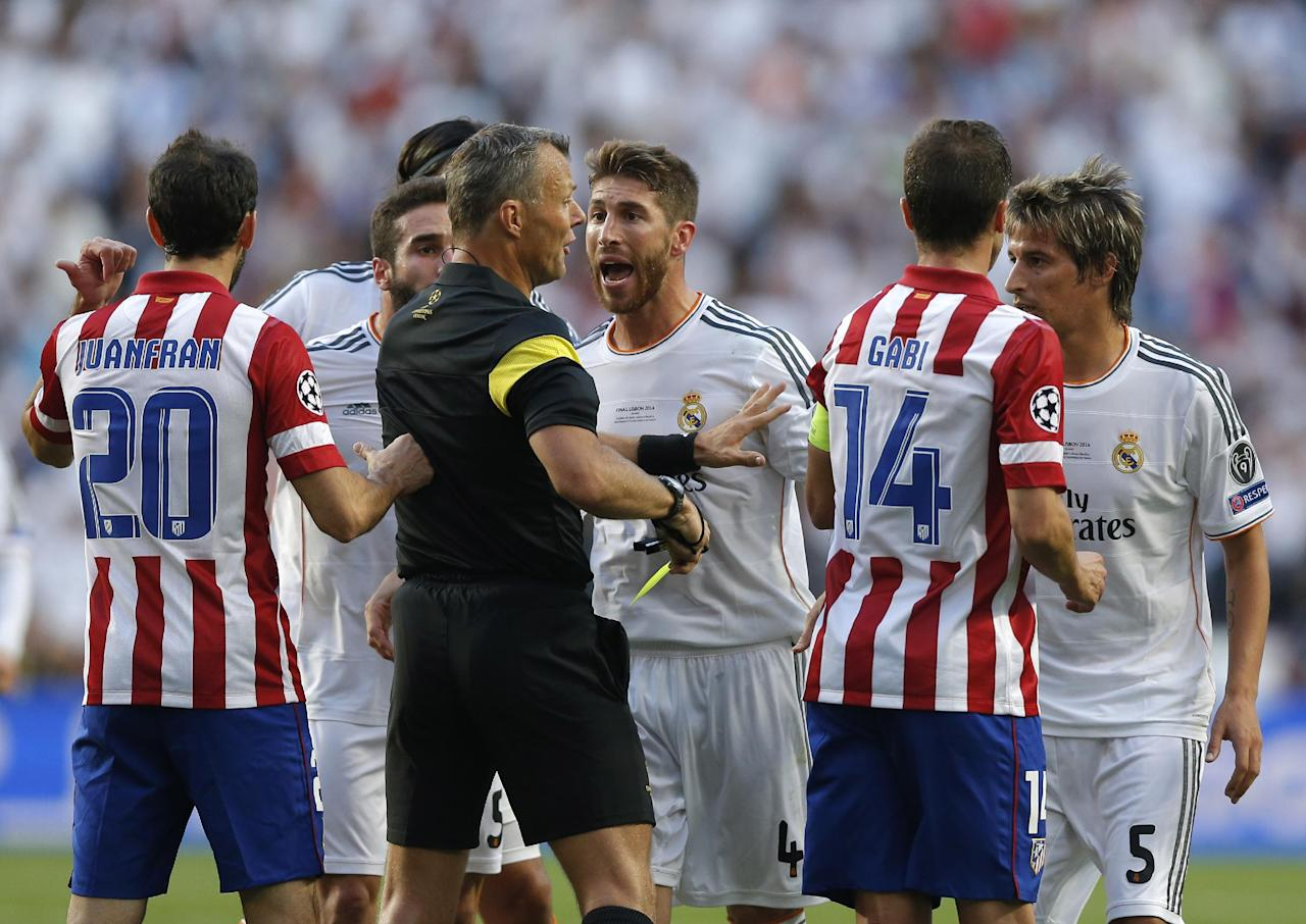 Real's Sergio Ramos, background centre is given a yellow card by referee Bjorn Kuipers,  during the Champions League final soccer match between Atletico de Madrid and Real Madrid, at the Luz stadium, in Lisbon, Portugal, Saturday, May 24, 2014. (AP Photo/Daniel Ochoa de Olza)