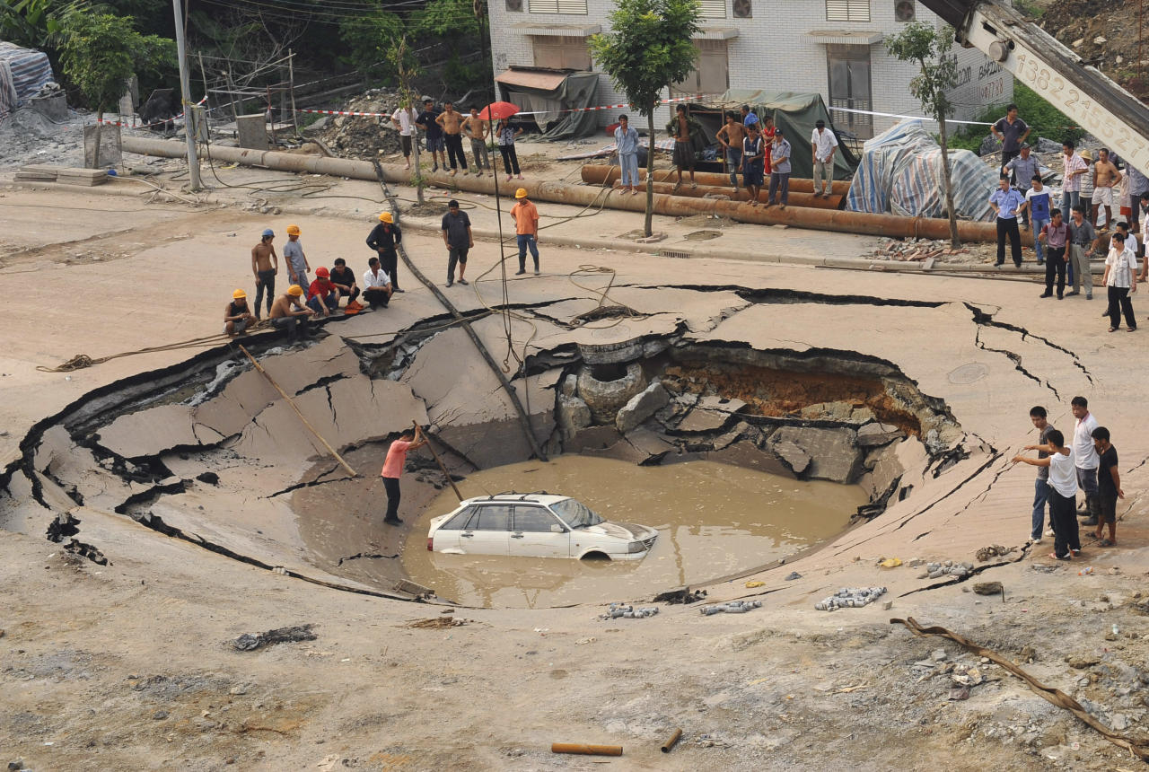 A stranded car is hoisted from a collapsed road surface in Guangzhou, Guangdong province, September 7, 2008. The road collapsed on Sunday afternoon and trapped the car in a hole, which measured 5 meters (16.4 feet) in depth and 15 meters (49.2 feet) in diameter, local media reported. Further investigation is underway. Picture taken September 7, 2008. REUTERS/China Daily (CHINA) CHINA OUT - RTX8JQR