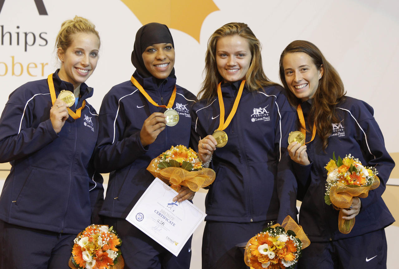 From left: Mariel Zagunis, Ibtihaj Muhammad, Dagmara Wozniak and Daria Schneider, of the United States, celebrate on the podium after winning a bronze medal in a women's team sabre final match at the World Fencing Championship in Catania, Italy, Saturday, Oct. 15, 2011. (AP Photo/Antonio Calanni)