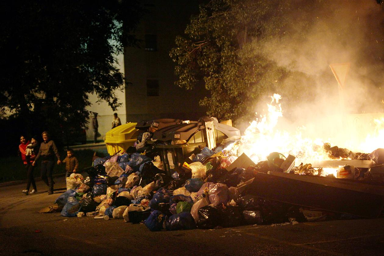 People walk past burning garbage piled up in the middle of the street in Jerez de la Frontera, Cadiz province in Andalucia, southern Spain.