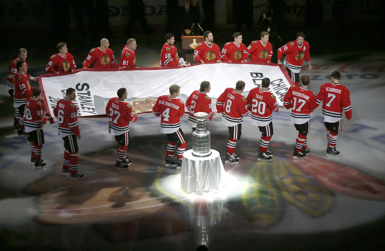The Chicago Blackhawks carry out the Stanley Cup Championship banner past the Stanley Cup during a ceremony before an NHL hockey game between the Blackhawks and the Washington Capitals, Tuesday, Oct. 1, 2013, in Chicago. (AP Photo/Charles Rex Arbogast)