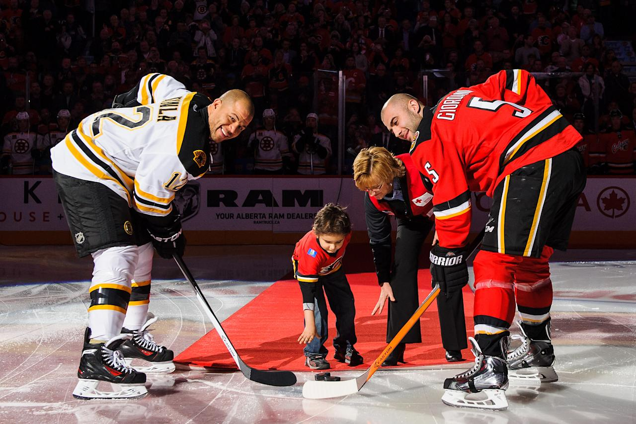 CALGARY, AB - DECEMBER 10: Mark Giordano #5 of the Calgary Flames and Jarome Iginla #12 of the Boston Bruins pose for the ceremonial face-off prior to an NHL game at Scotiabank Saddledome on December 10, 2013 in Calgary, Alberta, Canada. (Photo by Derek Leung/Getty Images)
