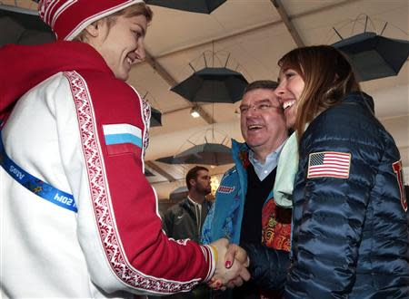 International Olympic Committee President Bach smiles as Russia's ice hockey player Gavrilova and U.S speed skater Ringsred introduce themselves during a visit in the Coastal Cluster Olympic Village in Sochi