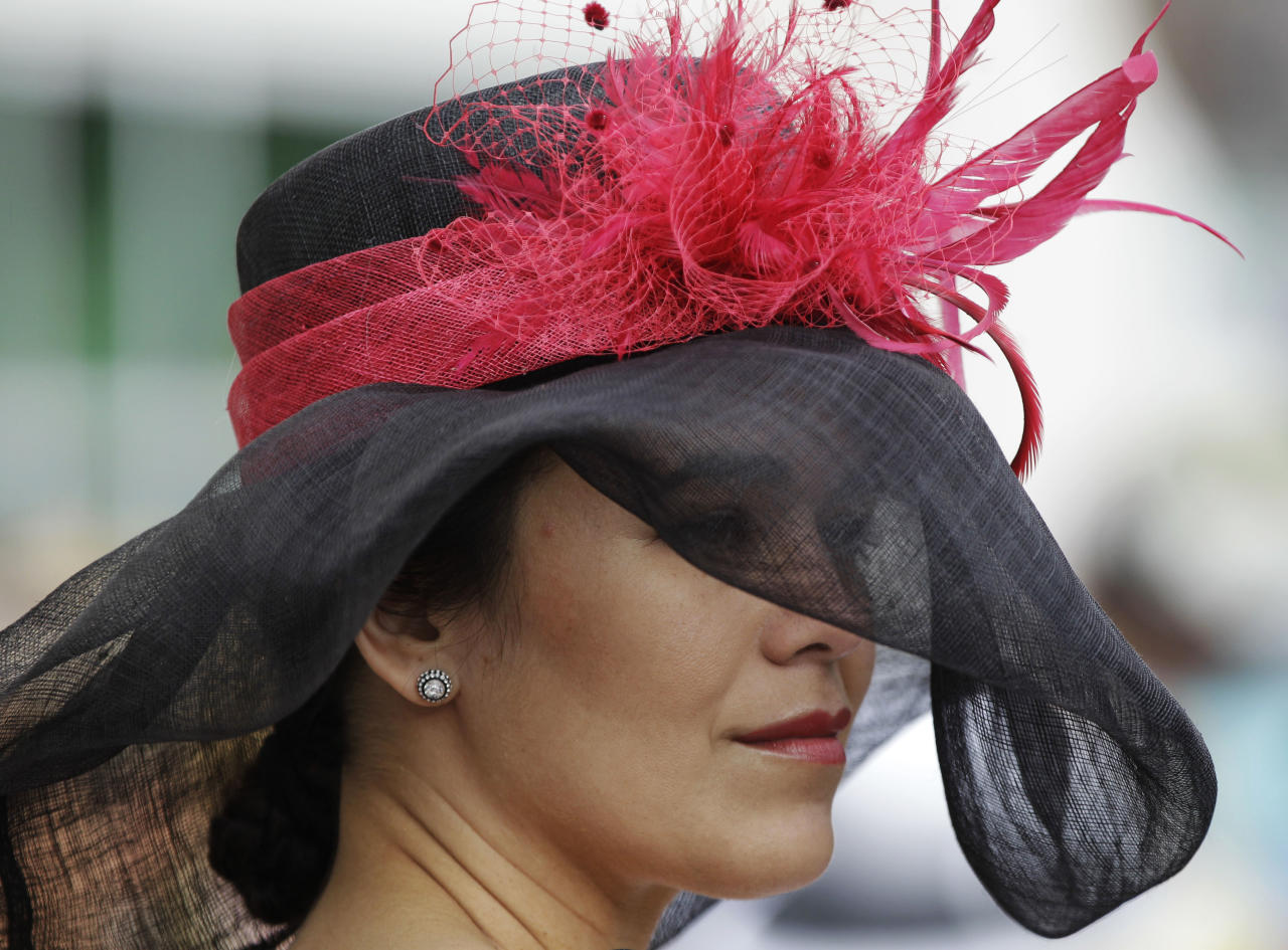 Jackie Resillez, from Cincinnati, waits for the start of the 138th Kentucky Derby horse race at Churchill Downs, Saturday, May 5, 2012, in Louisville, Ky. The Run for the Roses draws them to Churchill Downs. But what race goers wear is as much a spectacle in itself. (AP Photo/Mark Humphrey)