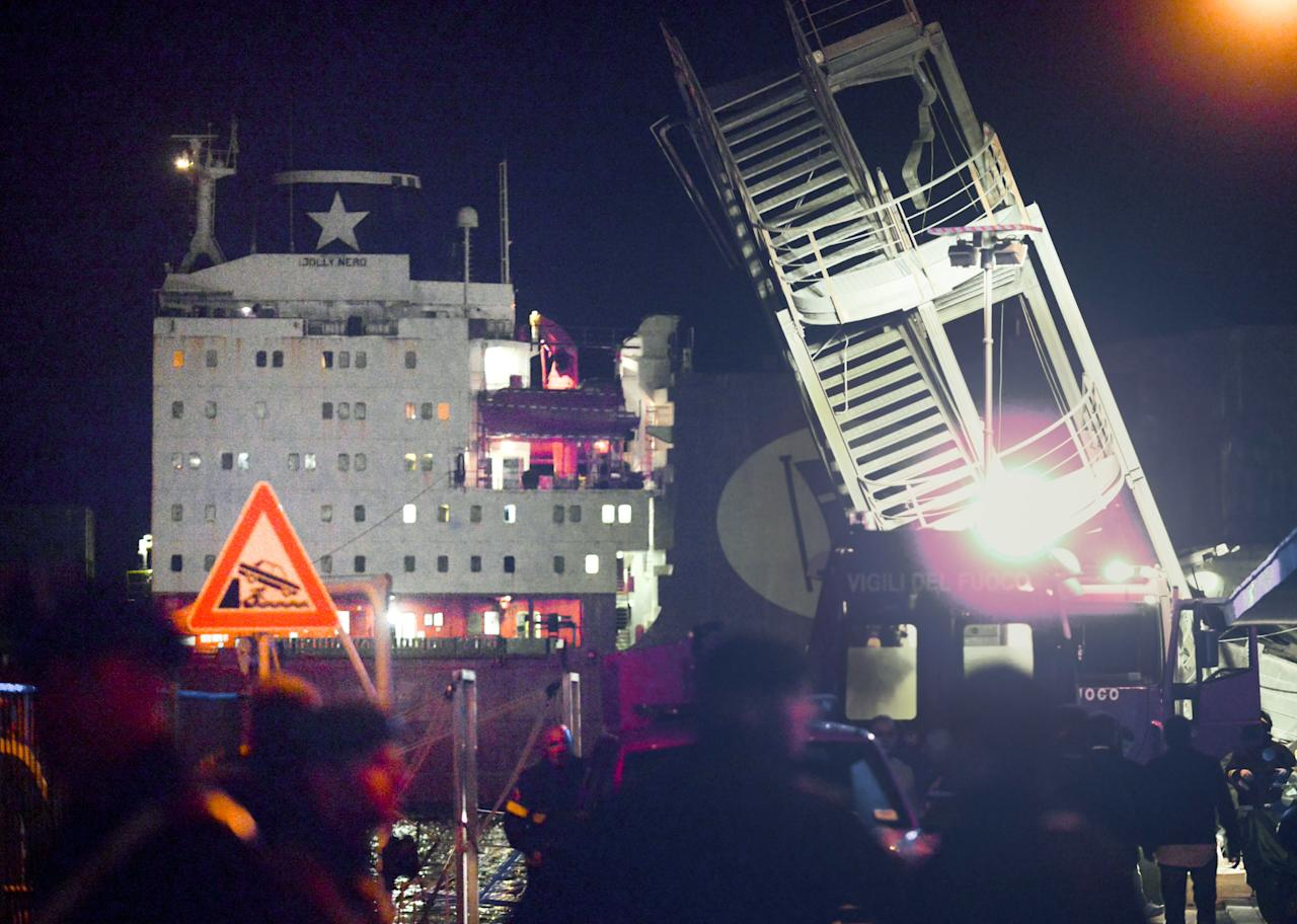 In this picture taken late Tuesday, May 7, 2013, the staircase of the control tower of the harbor of Genoa, northern Italy, is tilted after the cargo ship Jolly Nero, seen at left, crashed against the control tower of the port killing at least three people, rescue officials said Wednesday, May 8, 2013. Four others were hospitalized and a half-dozen people remained unaccounted for, including some feared trapped inside the submerged elevator of the control tower, officials said. (AP Photo/Marco Balostro)