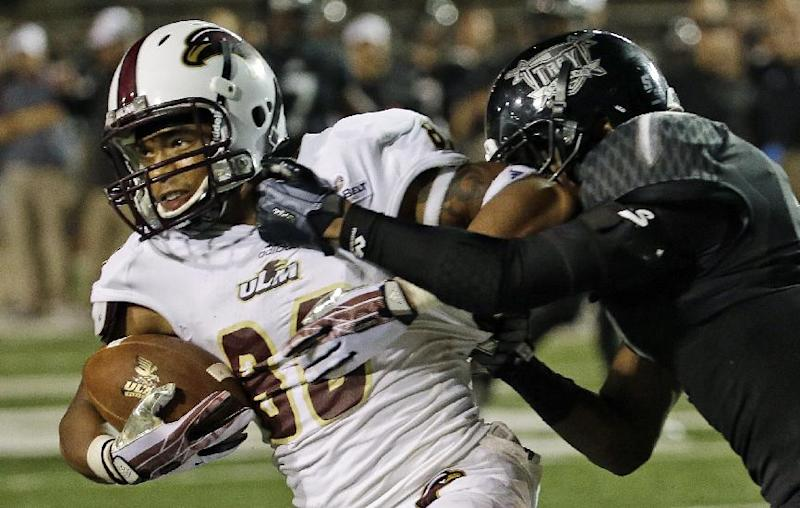 Louisiana-Monroe wide receiver Tre' Perrier (80) catches the game-winning touchdown as Troy cornerback Keion Payne defends during the second half of an NCAA college football game in Troy, Ala., Thursday, Oct. 31, 2013. Louisiana-Monroe beat Troy 49-37