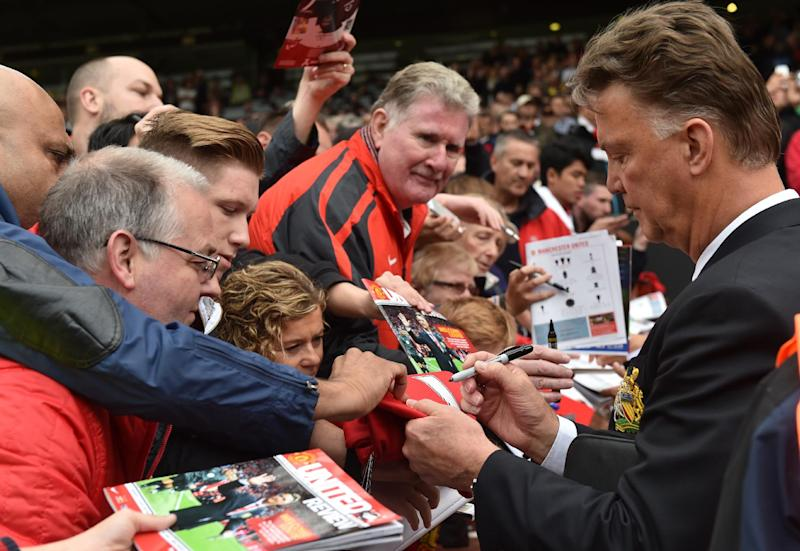 Manchester United's Dutch manager Louis van Gaal signs autographs at Old Trafford in Manchester on August 16, 2014