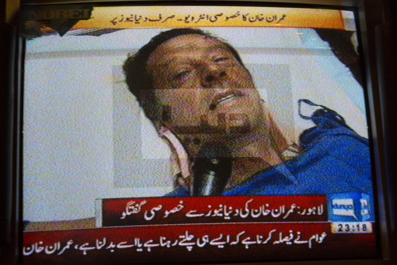 LAHORE, PAKISTAN - MAY 07: A television shows an image of Imran Khan, chairman of the Pakistan Tehrik e Insaf (PTI) party, giving an interview with a local television network as he lays in critical but stable condition after being injured from falling off a lifter during an election campaign rally on May 07, 2013 in Lahore, Pakistan. PTI chairman Imran Khan was injured at a rally in Lahore today after having fallen from a lifter. Pakistan's parliamentary elections are due to be held on May 11. Imran Khan of Pakistan Tehrik e Insaf (PTI) and Nawaz Sharif of the Pakistan Muslim League-N (PMLN) have been campaigning hard in the last weeks before polling. (Photo by Daniel Berehulak/Getty Images)