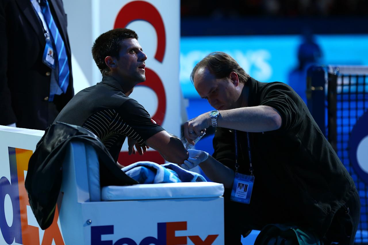 LONDON, ENGLAND - NOVEMBER 12:  Novak Djokovic of Serbia receives assistance for an injury after diving to reach a shot during his men's singles final match against Roger Federer of Switzerland during day eight of the ATP World Tour Finals at O2 Arena on November 12, 2012 in London, England.  (Photo by Matthew Lewis/Getty Images)