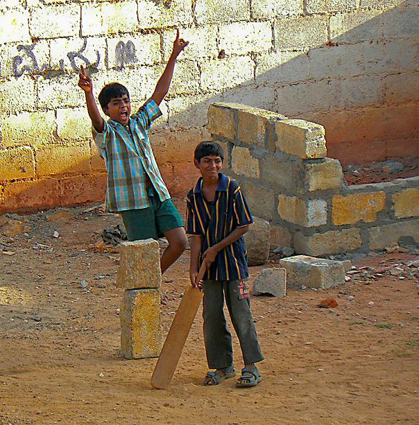 "Slum Cricket: This shot was taken while I was helping to set up a free school for slum children in Bangalore. I had to live on the fringe of the slum to make daily visits and to also for the slum dwellers to have faith in me and the school. Every afternoon was filled with the sound of cricket played all around my home. All of them knew me well as I was the ""Teacher Saab."" I was also a source of tennis balls to them so very popular at all times. They just ran when sometimes they broke my windows with a particularly well-hit but misdirected six. On this occasion the young batsman was declared out as the ball hit the concrete blocks and flew away. - by N V Rao"