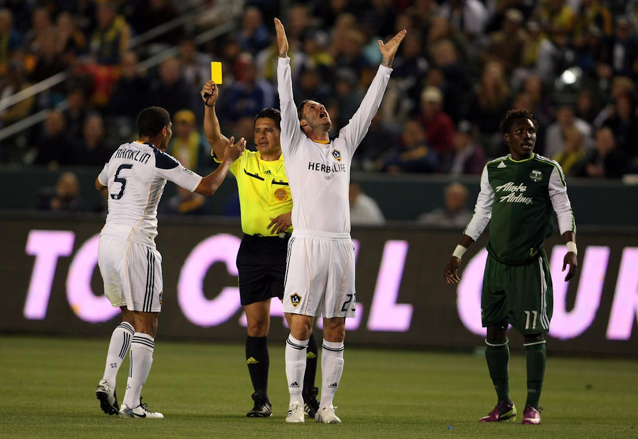 CARSON, CA - APRIL 23:  David Beckham #23 of the Los Angeles Galaxy reacts as teammate Sean Franklin #5 receives a yellow card from referee Ramon Hernandez for a foul on Kalif Alhassan #11 of the Portland Timbers in the first half during the MLS match at The Home Depot Center on April 23, 2011 in Carson, California. The Galaxy defeated the Timbers 3-0. (Photo by Victor Decolongon/Getty Images)