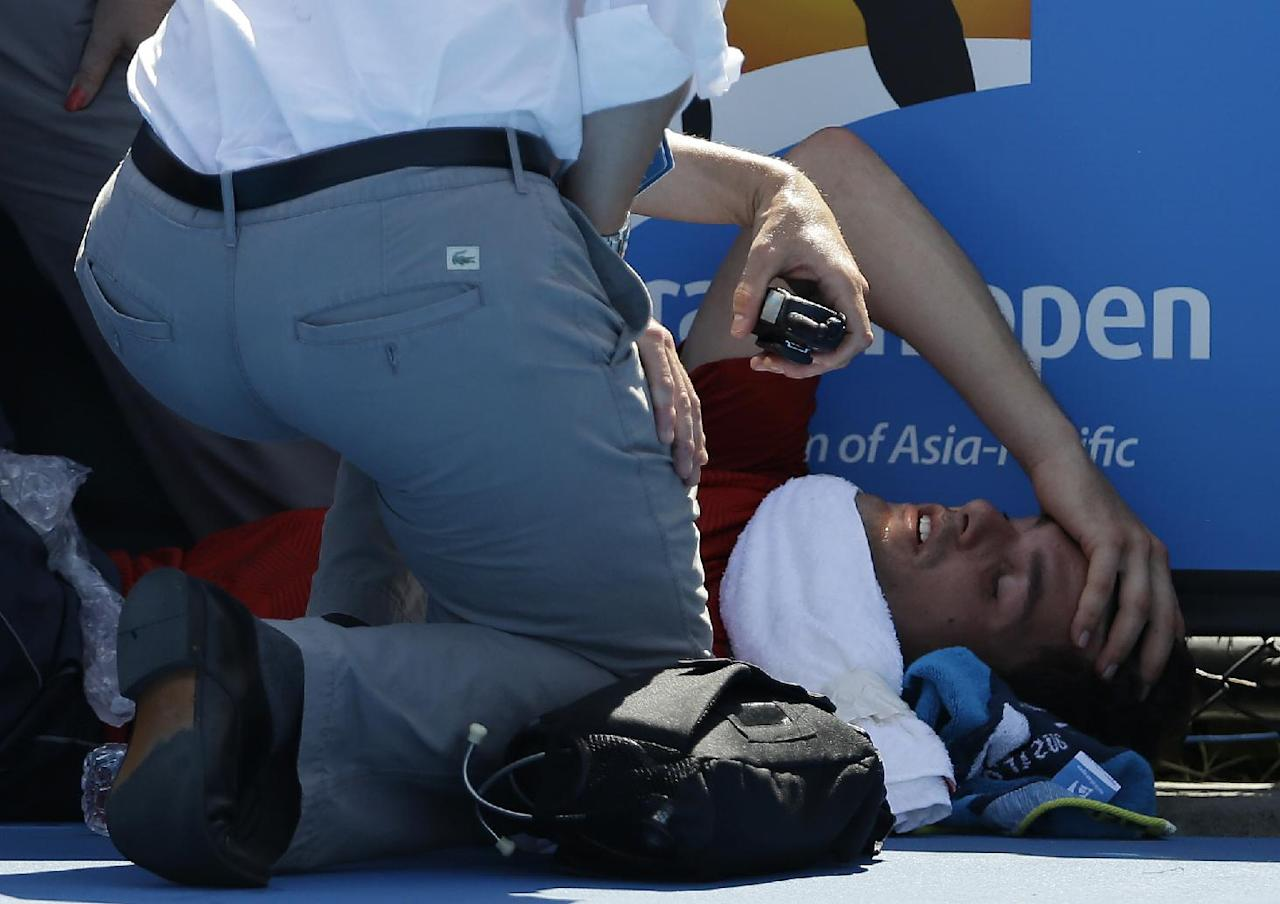 Frank Dancevic of Canada lies on the court after collapsing during his first round match against Benoit Paire of France as temperatures topped at 43 C (108 F) at the Australian Open tennis championship in Melbourne, Australia, Tuesday, Jan. 14, 2014. (AP Photo/Aijaz Rahi)
