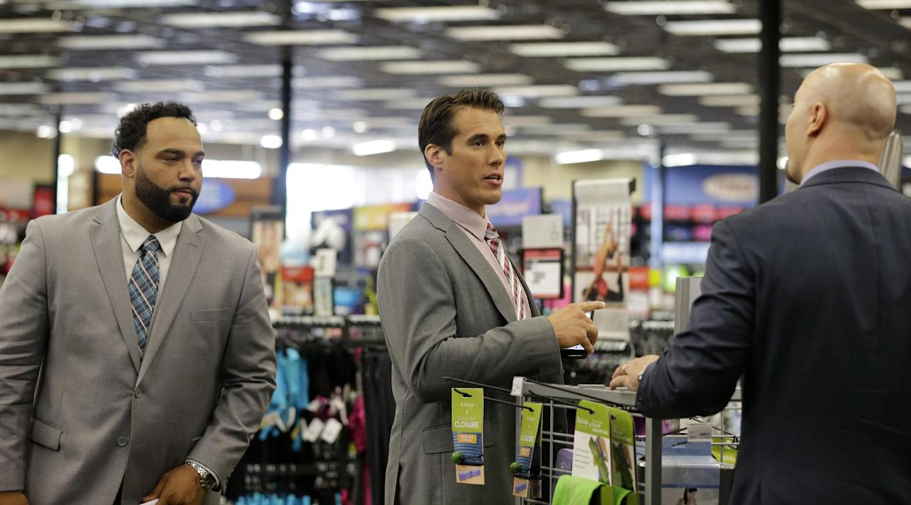 In this photo taken on Wednesday, June 18, 2014, former first-round draft pick, quarterback Brady Quinn, center, waits with fellow NFL football player defensive tackle Antonio Garay, left, at a sporting goods store during the NFL's Broadcast Boot Camp in Mount Laurel, N.J. Twenty-five current and former players participating in the NFL's Broadcast Boot Camp this week, are vying for broadcasting gigs. (AP Photo/Mel Evans)