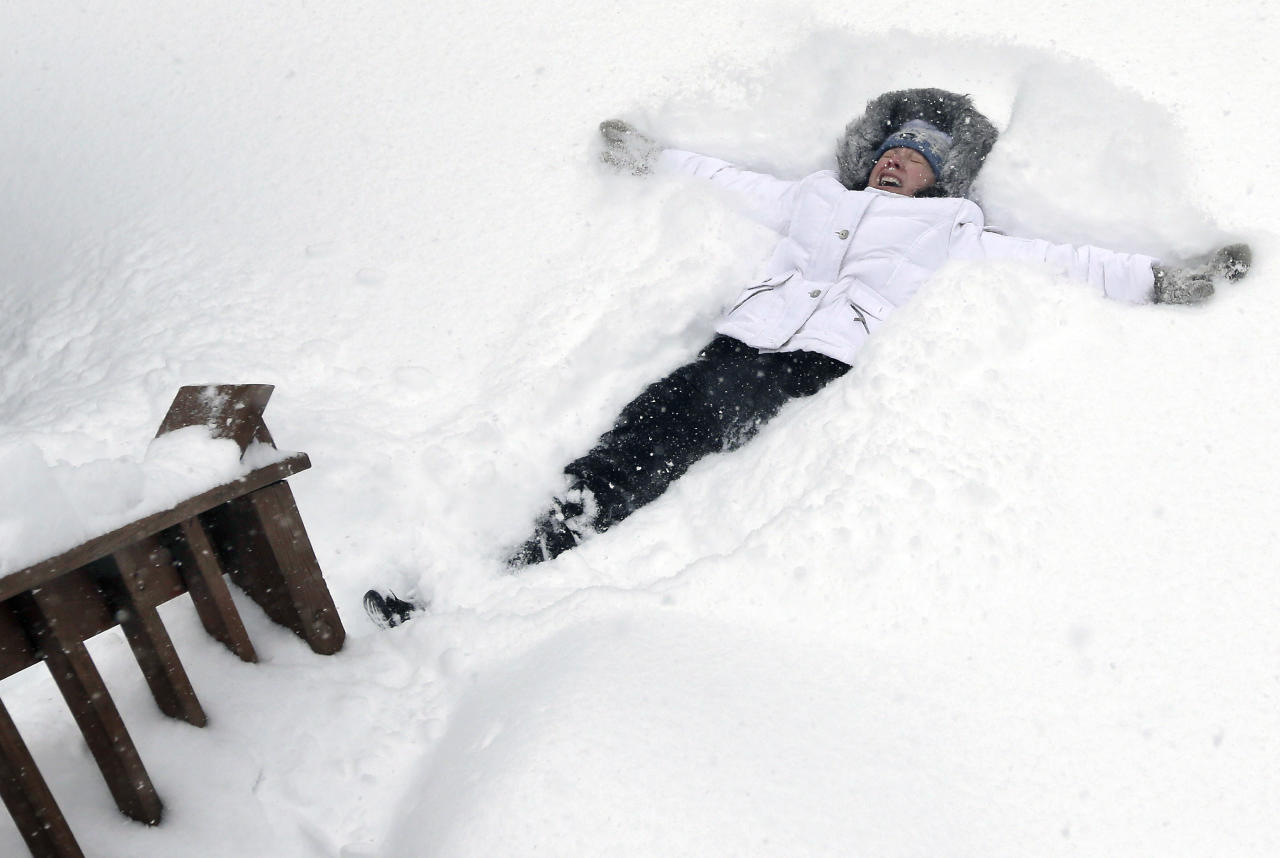 Nicole Lacoursiere of North Andover, Mass. falls back to make a snow angel Saturday, Feb. 9, 2013 in some 24 inches of snow that had fallen in her yard. A behemoth storm packing hurricane-force wind gusts and blizzard conditions swept through the Northeast, dumping more than 2 feet of snow on New England and knocking out power to 650,000 homes and businesses. (AP Photo/Elise Amendola)