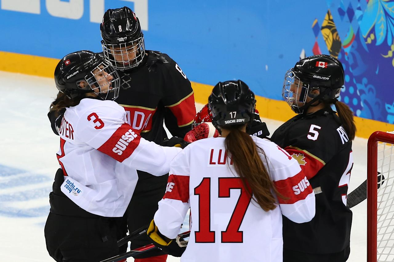 SOCHI, RUSSIA - FEBRUARY 08: Sarah Forster #3 of Switzerland fights with Lauriane Rougeau #5 of Canada during the Women's Ice Hockey Preliminary Round Group A Game on day 1 of the Sochi 2014 Winter Olympics at Shayba Arena on February 8, 2014 in Sochi, Russia. (Photo by Martin Rose/Getty Images)