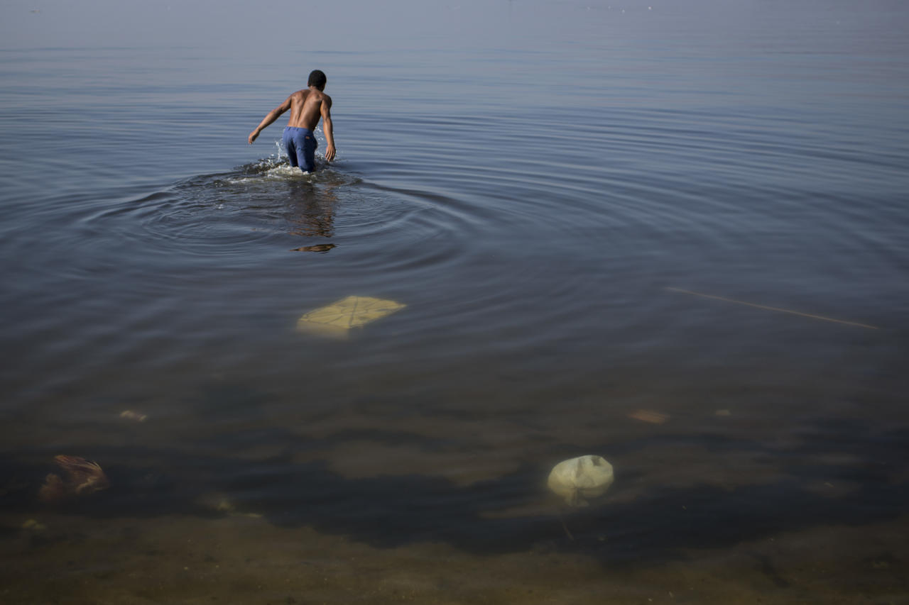 In this May 15, 2014 photo, a man jumps into the polluted waters of Guanabara Bay in Rio de Janeiro, Brazil. Brazil will not make good on its commitment to clean up Rio de Janeiro's sewage-filled Guanabara Bay by the 2016 Olympic Games, state environmental officials acknowledged in a letter obtained Saturday May 17, 2014, by The Associated Press. (AP Photo/Felipe Dana)