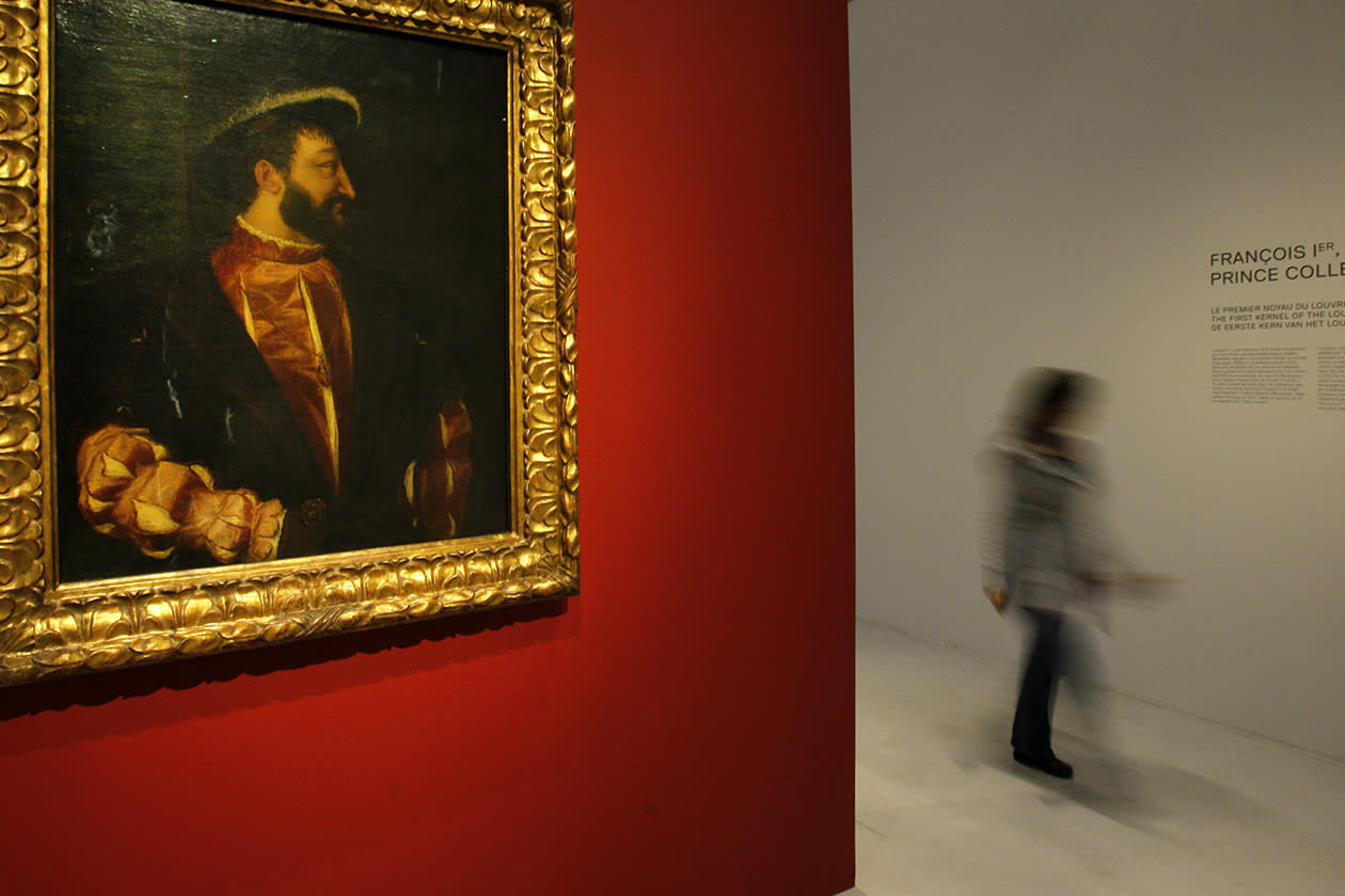 "A woman walks past "" Francois 1er, Roi de France""  a painting by Tiziano Vecellio, ( Titien ) in the Louvre Museum in Lens."