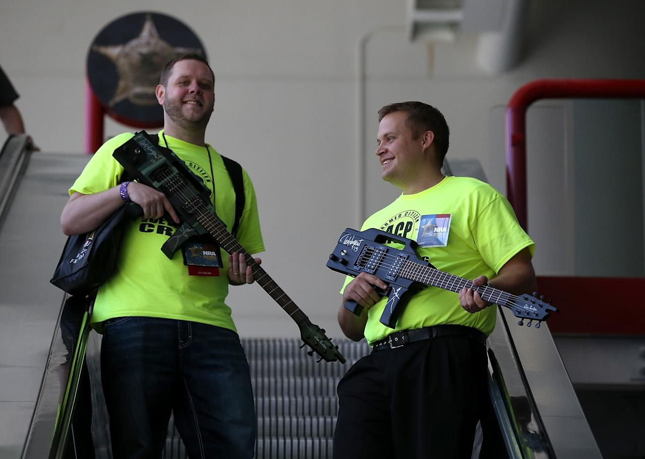HOUSTON, TX - MAY 05:  Attendees carry guitars that look like assault rifles as they ride an escalator during the 2013 NRA Annual Meeting and Exhibits at the George R. Brown Convention Center on May 5, 2013 in Houston, Texas.  More than 70,000 people attended the NRA's 3-day annual meeting that featured nearly 550 exhibitors, a gun trade show and a political rally.  (Photo by Justin Sullivan/Getty Images)