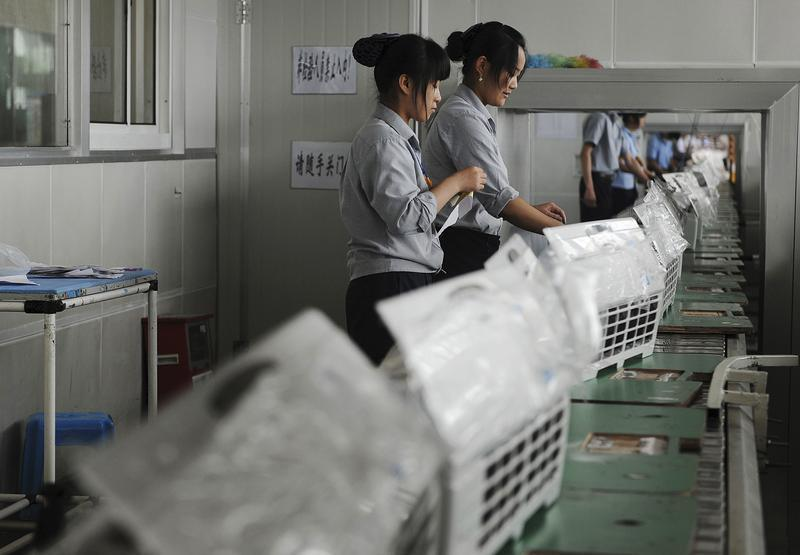 Employees make air-conditioners along a production line at a factory in Hefei