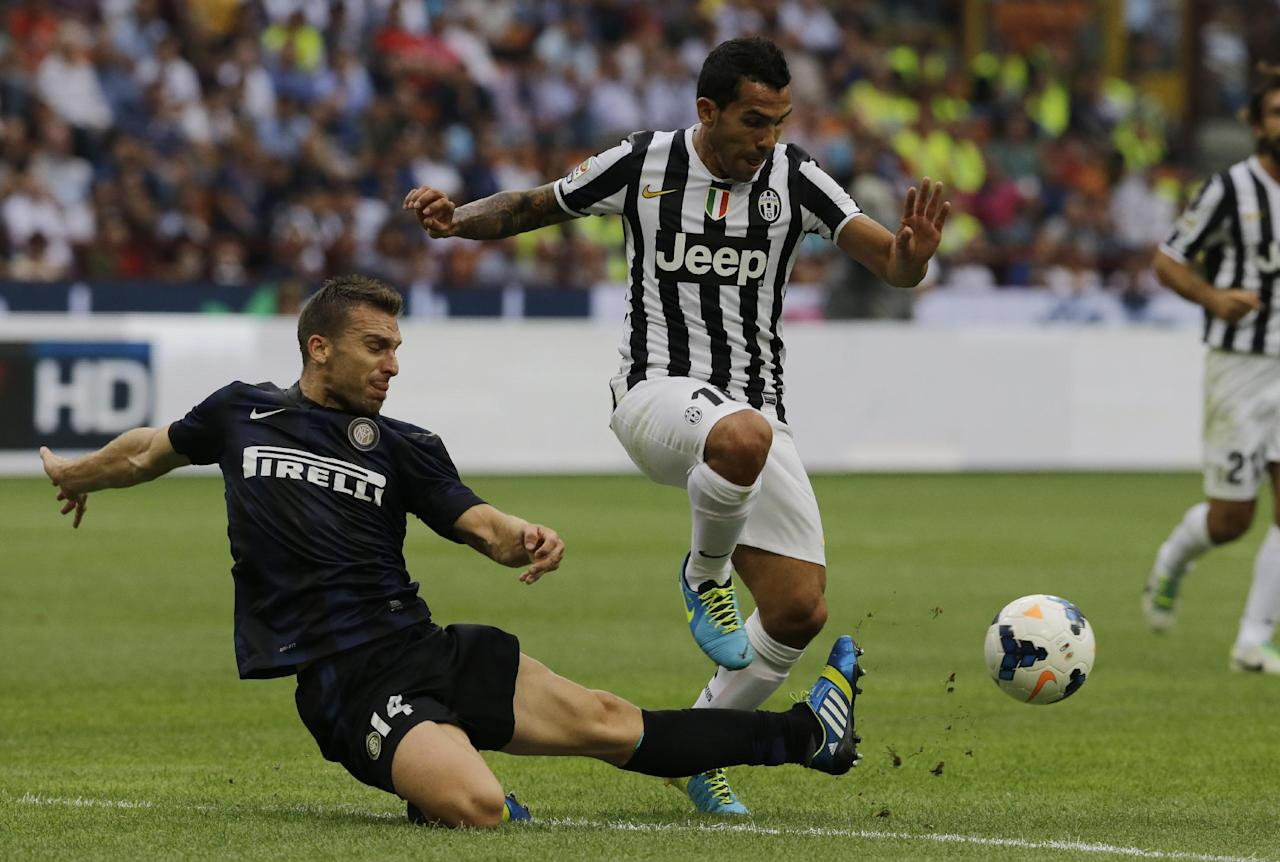 Juventus forward Carlos Tevez of Argentina, right, is tackled by Inter Milan defender Hugo Campagnaro, of Argentina, during a Serie A soccer match between Inter Milan and Juventus, at the San Siro stadium in Milan, Italy, Saturday, Sept. 14, 2013. (AP Photo/Luca Bruno)