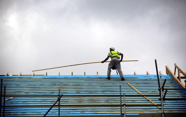 Construction workers work on a building on the edge of Glastonbury on September 3, 2012 in Somerset, England. Critics of the government's plans to relax planning laws to help kick start the economy are claiming it could lead to more development in sensitive rural and protected greenbelt areas. The chancellor, George Osborne, has called for deregulation of planning laws, raising the prospect of allowing more development of green belt land, which has angered many who have campaigned for protected green belts around urban areas to remain free of development. (Photo by Matt Cardy/Getty Images)