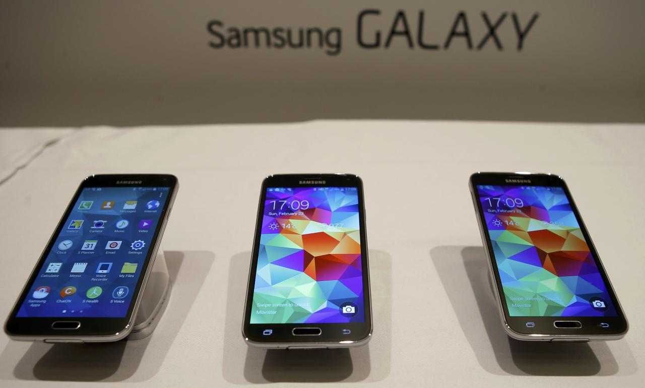 New Samsung Galaxy S5 smartphones are seen on a display at the Mobile World Congress in Barcelona February 23, 2014. Samsung Electronics unveiled a new smart watch and fitness band along with the latest version of its flagship Galaxy smartphone on Monday, demonstrating how the battleground for innovation is shifting from the hand to the wrist.Picture taken on February 23. REUTERS/Albert Gea (SPAIN - Tags: BUSINESS TELECOMS)