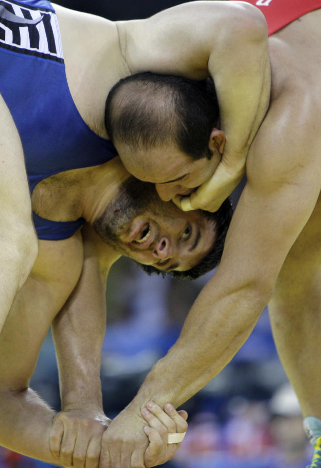 Iran's Fardin Masoumi, right, wrestles Kazakhstan's Marid Mutalimov in a bronze medal 120 kilogram freestyle match at the 2008 Olympics in Beijing, Thursday, Aug. 21, 2008. Mutalimov won the bronze. (AP Photo/David Guttenfelder)