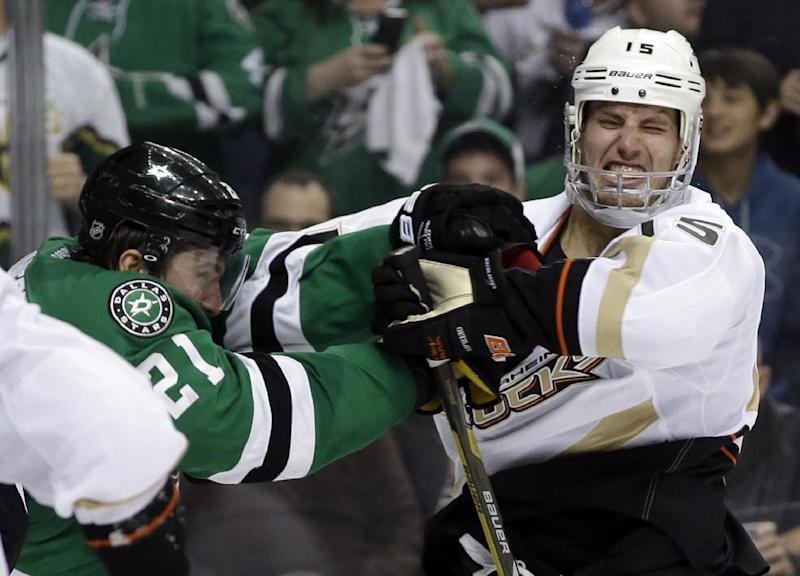 Anaheim Ducks center Ryan Getzlaf (15) recoils from a punch to the mask by Dallas Stars' Antoine Roussel (21) of France in the second period of Game 3 of a first-round NHL hockey Stanley Cup playoff series game, Monday, April 21, 2014, in Dallas