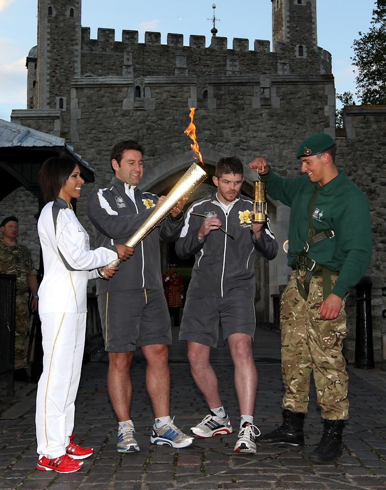 LONDON, ENGLAND - JULY 20:   Dame Kelly Holmes lights her torch as Marine Martyn Williams holds the flame during the London 2012 Olympic Torch Relay on July 20, 2012 in London, England. The Olympic Flame is now on day 63 of a 70-day relay involving 8,000 torchbearers covering 8,000 miles. (Photo by Jan Kruger/Getty Images)