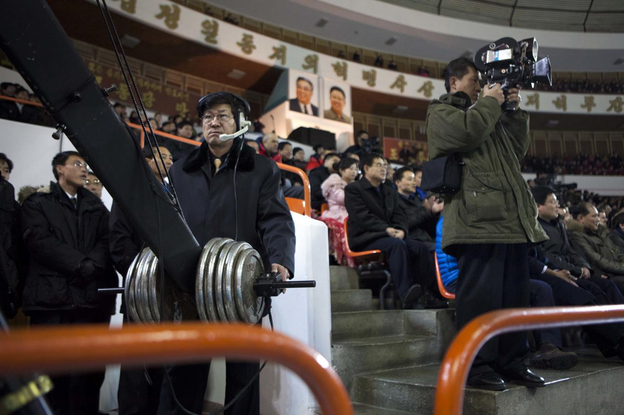 North Korean cameramen use an elevated boom camera, left, and a older film camera, right, to cover the opening ceremony of a figure skating exhibition event at an ice skating rink in Pyongyang, North Korea on Friday, Feb. 15, 2013. (AP Photo/David Guttenfelder)