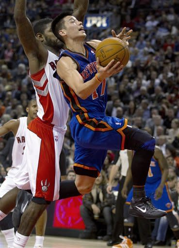 New York Knicks guard Jeremy Lin (17) drives against Toronto Raptors forward Amir Johnson during the first half of an NBA basketball game in Toronto on Tuesday, Feb. 14, 2012. (AP Photo/The Canadian Press, Frank Gunn)