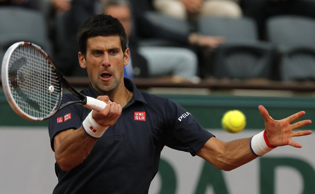 Serbia's Novak Djokovic returns the ball to Canada's Milos Raonic during their quarterfinal match of  the French Open tennis tournament at the Roland Garros stadium, in Paris, France, Tuesday, June 3, 2014. Djokovic won 7-5, 7-6, 6-4. (AP Photo/Michel Spingler)