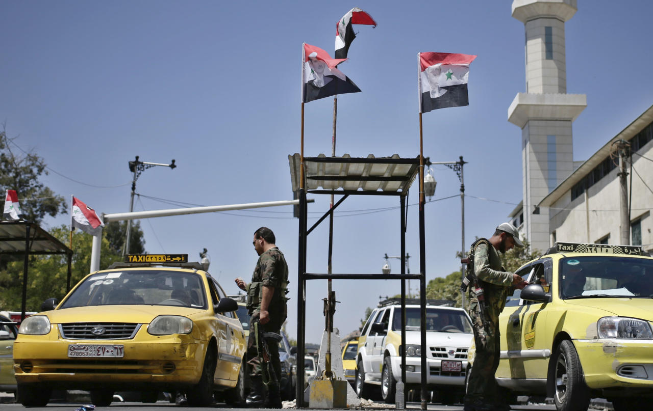 """Syrian military soldiers check identifications of taxi drivers at a check point on Baghdad street, in Damascus, Syria, Wednesday, Aug. 21, 2013. Syrian opposition groups claimed scores have died on Wednesday in a government offensive near Damascus, attacks in which some activists say regime troops used """"poisonous gas."""" The government denied the reports. (AP Photo/Hassan Ammar)"""