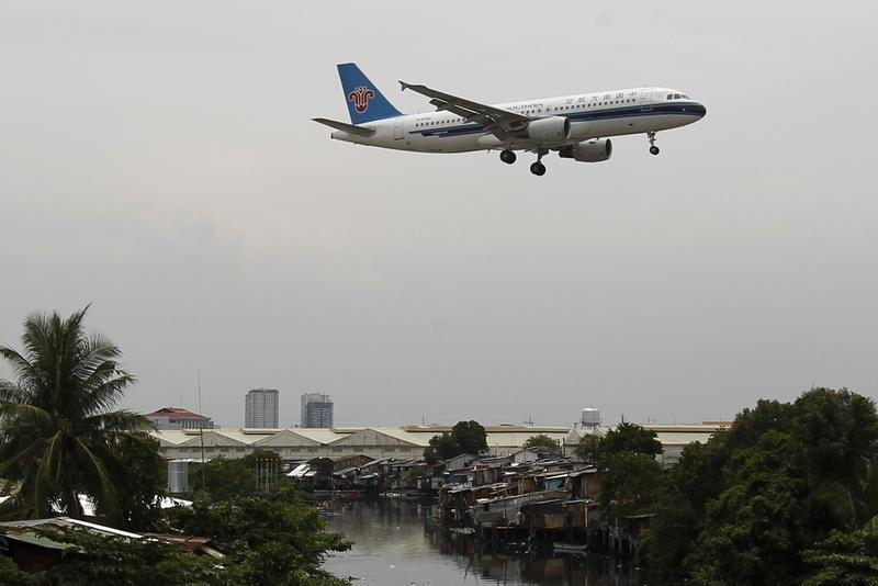 A China Southern Airlines aircraft flies over a slum before landing at Manila's International airport