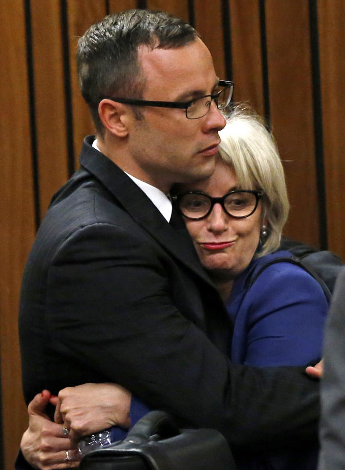 Oscar Pistorius and his aunt Lois Pistorius, right, hug after the prosecution closed it case in court in Pretoria, South Africa, Tuesday, March 25, 2014. Pistorius is charged with the Valentines Day 2013 shooting death of his girlfriend Reeva Steenkamp. The trial will resume Friday. (AP Photo/Siphiwe Sibeko, Pool)