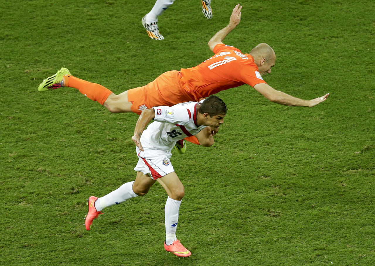 Netherlands' Arjen Robben, top, falls over Costa Rica's Cristian Gamboa during the World Cup quarterfinal soccer match between the Netherlands and Costa Rica at the Arena Fonte Nova in Salvador, Brazil, Saturday, July 5, 2014. (AP Photo/Themba Hadebe)